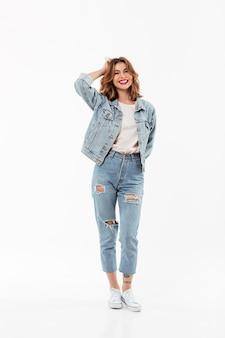 Полная длина жизнерадостная женщина в джинсовой одежде позирует на белой стене