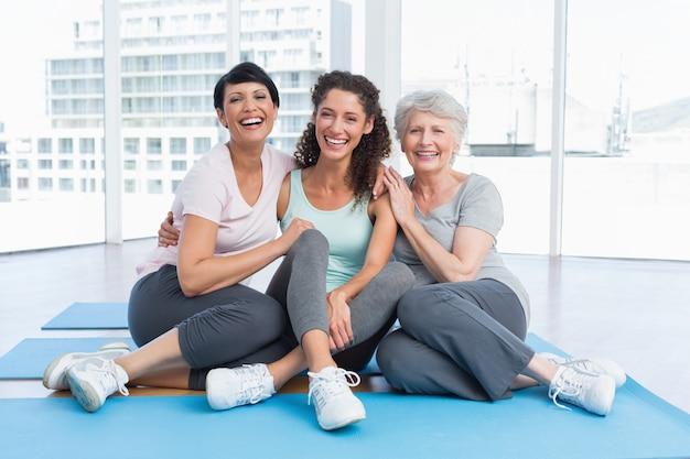 Full length of cheerful women in yoga class