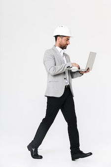 Full length of a confident bearded man builder wearing suit and hardhat standing isolated over white wall, using laptop computer
