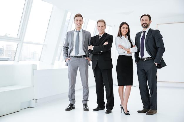 Полная уверенная деловая команда стоит в офисе
