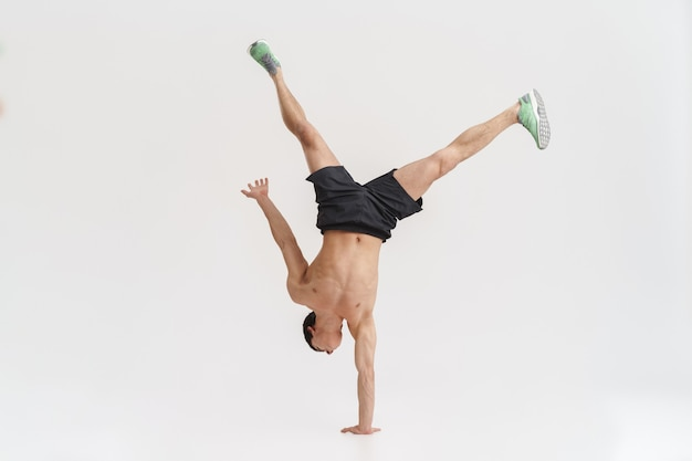 Full length of a confident fit sportsman doing acrobatic tricks over white
