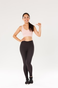Full length of confident smiling asian female athelte in sportsbra and leggigns, fitness girl pointing at herself, lead active and healthy lifestyle, being professional, standing white background.