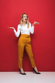 Full length of a confused beautiful young blonde woman standing isolated over red background, holding mobile phone