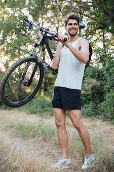 Full length cyclist holding bicycle on forest road
