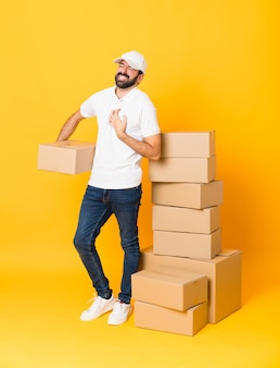 Full length  delivery man among boxes over isolated yellow wall having a pain in the heart