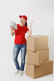 Full length of delivery woman in red cap, t-shirt isolated on white background. female courier near empty cardboard boxes, bundle of dollars, cash money. receiving package. copy space advertisement.