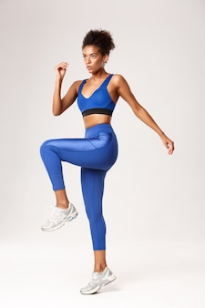 Full length of determined fitness girl in blue sportswear workout in gym, looking serious, standing