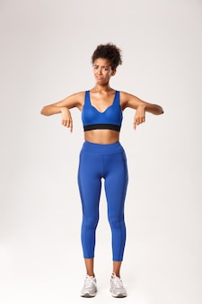 Full length of disappointed african-american girl in blue sports outfit, pointing fingers down and
