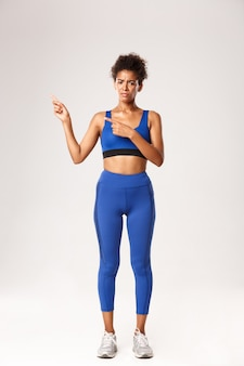 Full length of disappointed african-american girl in sportswear, looking upset, frowning and