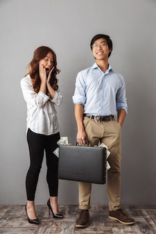 Full length of excited asian couple standing, holding briefcase full of money banknotes