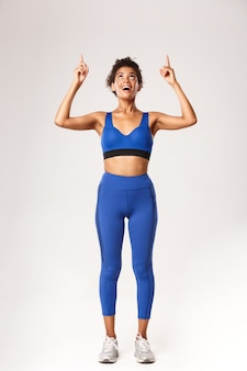 Full length of excited and happy african-american woman in sportswear for workout, looking and
