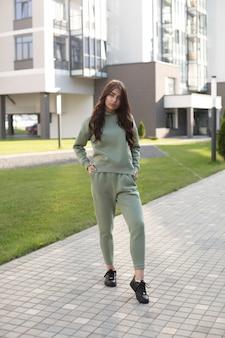 トレンディなオリーブのスウェットシャツとストリートでスニーカーとジョガーを身に着けている長い茶色の髪のフルレングスのファッションモデル。