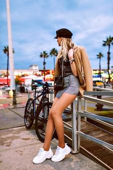 通り、春秋の時間、トレンディな服やアクセサリーでポーズをとって、長い日焼けした脚を持つ見事なスタイリッシュなブロンドの女性の完全な長さのファッションの肖像画
