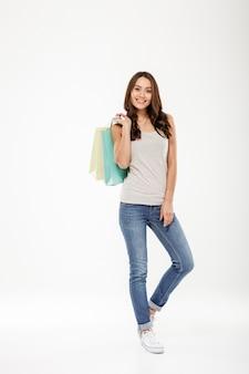 ショッピングと白い壁に分離されたカメラで見た後商品とパッケージを保持しているフルレングスのファッション女性