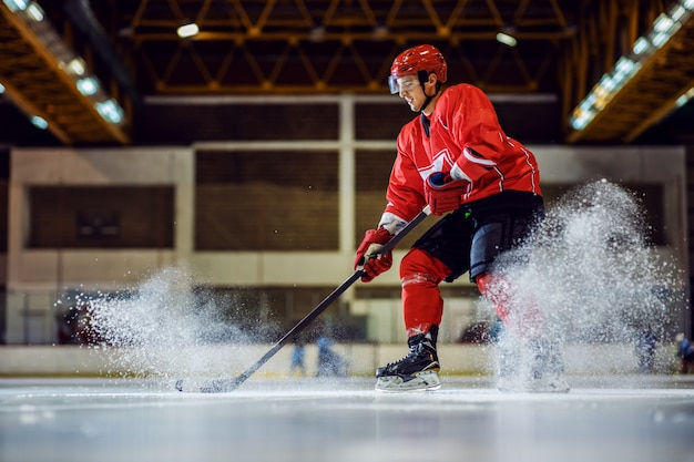 Full length of fearless hockey player skating and trying to make a score. hall interior. winter sports.