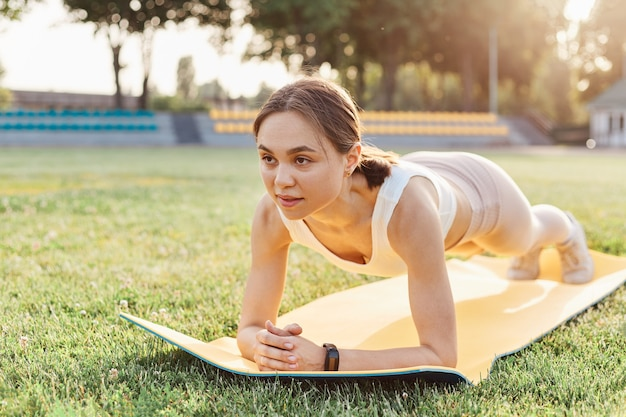 Full length, fit beautiful woman wearing white top and beige leggins, training on mat outdoor in summer day