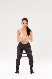 Full length of focused good-looking female athelte, asian fitness girl perform squats with clasped hands and resistance stretching band on thighs, using workout equipment during training session