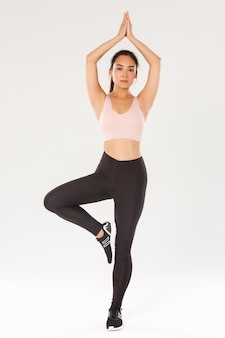 Full length of focused, slim brunette asian girl in fitness outfit practice yoga. girl lifting arms above head and standing in asana pose, white background.