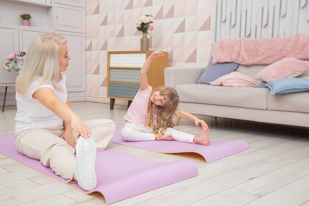 Полная длина вид спереди улыбающаяся белокурая мать на коврике для йоги с милой игривой маленькой дочкой дошкольного возраста делают различные упражнения. счастливая мама упражнениями йоги с маленьким ребенком.