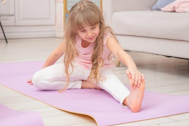 ヨガマットの上に座っているかわいい遊び心のある小さな就学前の女の子の笑顔の全身正面図は、さまざまな運動を行います。自宅でヨガを練習する幸せな子供。