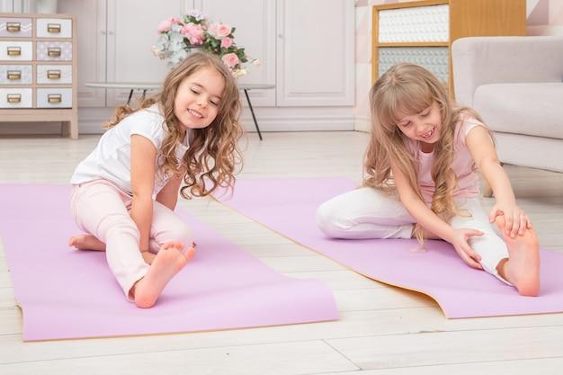 전체 길이 전면보기 요가 매트에 앉아 귀여운 장난기 어린 유치원 여자를 웃 고 다양 한 운동을합니다.