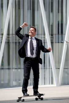 Full length fun businessman standing on skateboard with arm outstretched