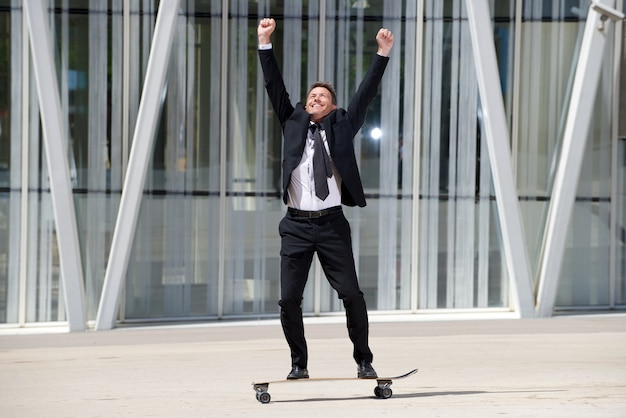 Full length fun businessman standing on skateboard with arms raised