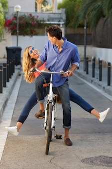 Full length fun couple riding bicycle together on path
