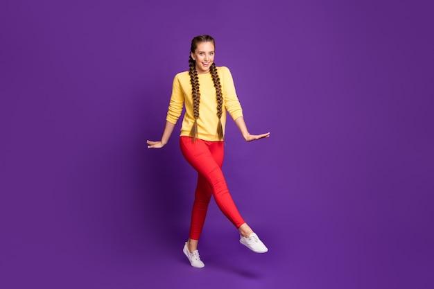 Полная длина смешная миллениал дама идет по улице длинные косы удивительно теплый солнечный день носить повседневный желтый пуловер красные брюки изолированы фиолетового цвета стена