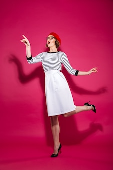 Full length ginger woman in eyeglasses pointing and looking away over pink