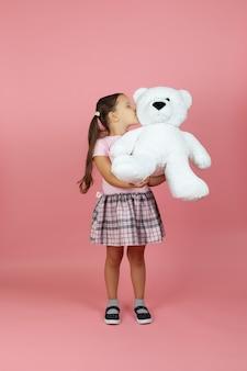 フルレングスの女の子が白いテディベアを持ってキスします