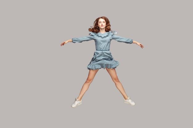 Девушка в полный рост парит в воздухе, раздвинув руки, ноги как звезда, прыгает на батуте