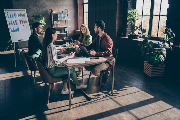 Full length  of group people sit desk table have briefing discussing enterprise development man suggest great progress ideas in modern office workstation