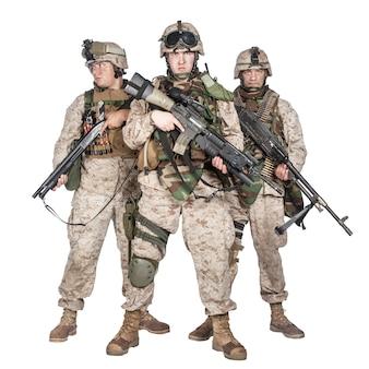 軍の特殊作戦部隊の兵士、戦闘服を着た海兵隊員、戦術的な弾薬、制式小銃、ショットガン、ミドルマシンガンで武装したスタジオ撮影の全身像