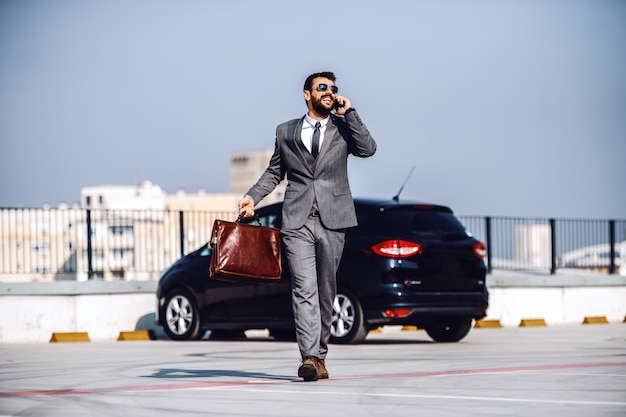 Full length of handsome caucasian bearded businessman in suit and with sunglasses walking on parking lot, talking on the phone and holding briefcase.