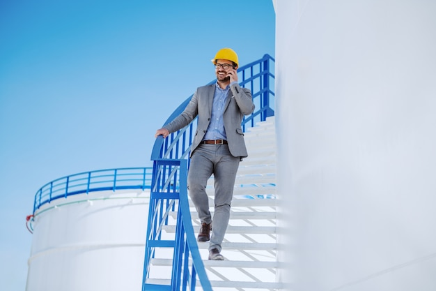 Full length of handsome caucasian businessman in suit and helmet on head going down the stairs on oil tank storage and talking on the phone.