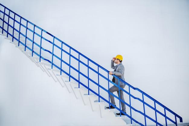 Full length of handsome caucasian businessman with helmet on head climbing oil storage tank.