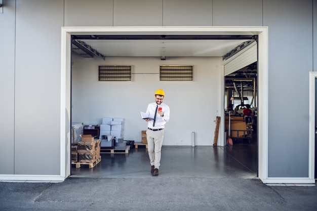 Full length of handsome caucasian supervisor in shirt and tie and with helmet on head