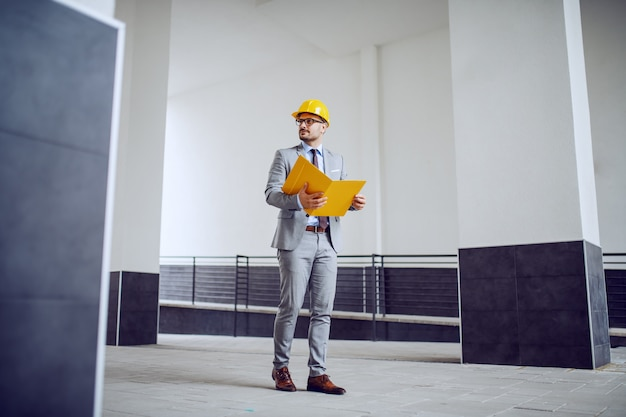 Full length of handsome classy unshaven male architect in suit and with helmet on head walking outdoors with folder in hands.
