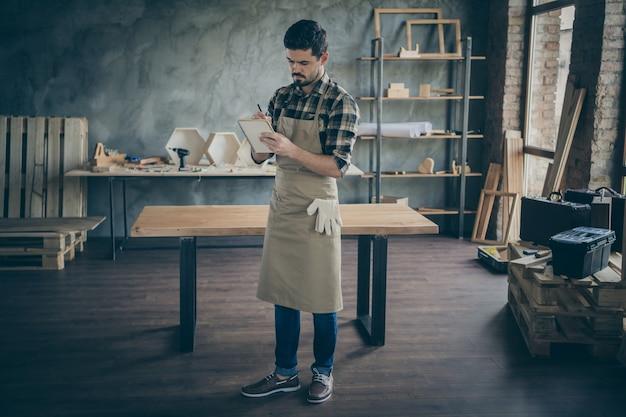 クライアントの注文の希望の詳細に気づいたフルレングスのハンサムな焦点を絞った男販売管理者紙日記ペン木製ビジネス産業木工店ガレージ屋内
