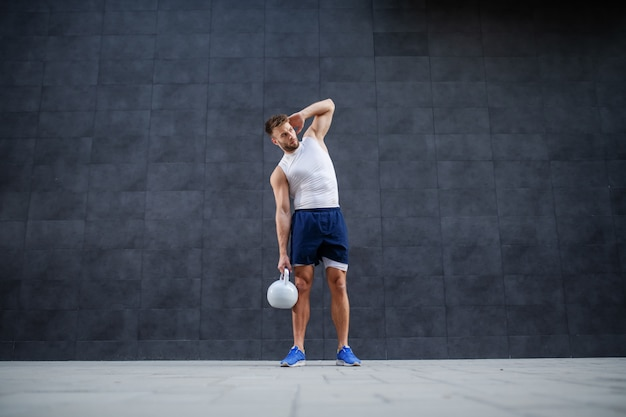 Full length of handsome strong muscular bearded caucasian man in shorts and t-shirt posing with kettle bell while standing outdoors in front of gray wall.