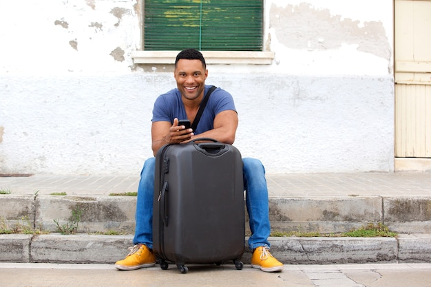 Full length handsome young african man sitting with suitcase and smart phone