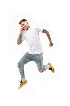 Integrale del bel giovane che prende il telefono mentre salta contro il fondo arancio dello studio.