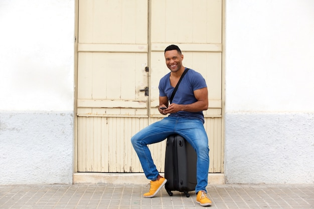 Full length happy african man sitting on a suitcase with mobile phone and smiling