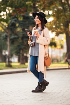 Full length of happy asian woman in stylish wear holding mobile phone and coffee cup while standing in park outdoor