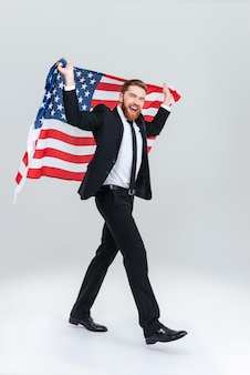 Полный счастливый бородатый деловой человек в черном костюме держит флаг сша сзади. вид сбоку. изолированный серый фон