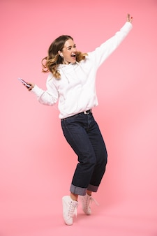 Full length happy blonde woman wearing in casual clothes listening to music and dancing over pink wall