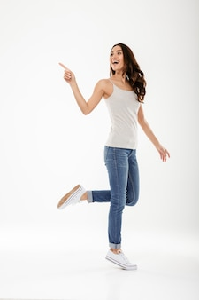 Full length of happy brunette woman pointing and looking away over gray
