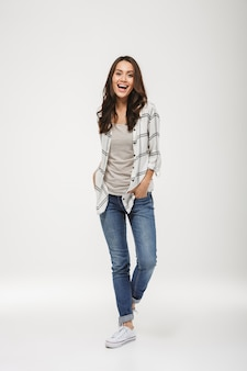 Full length happy brunette woman in shirt posing with arms in pockets and looking at the camera over gray
