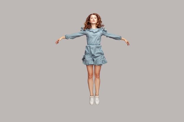 Полная длина счастливая спокойная симпатичная девушка, парящая в воздухе с поднятыми руками, как крылья